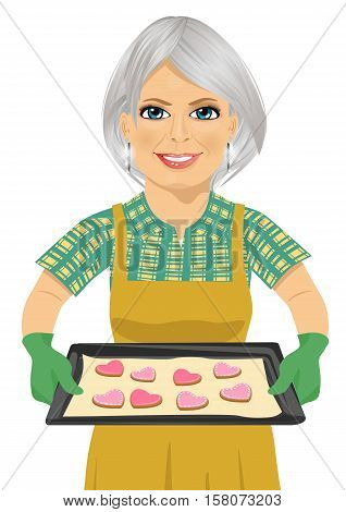 senior woman holding baking tray with heart shape cookies over white background