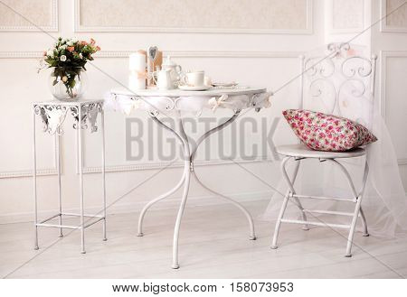 dining white room interiour with iron table and chair coffee cup set pillow and flowers in vase