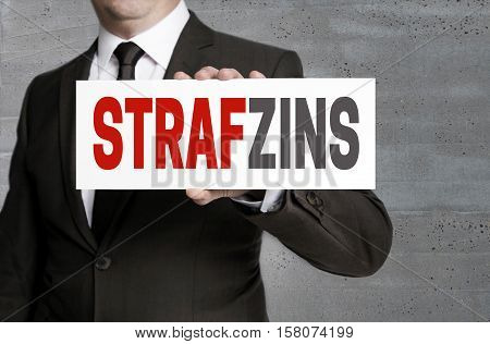 Strafzinz (in German Negative Interest) Sign Is Held By Businessman