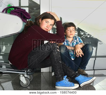 two teen sibling boy and girl brother and sister with trolley in the airport sad waiting for delayed fligt back home
