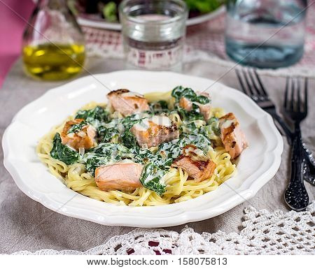 Pasta with salmon fish and creamy spinach sauce