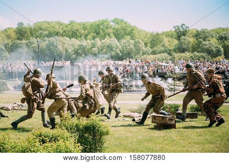 Gomel, Belarus - May 9, 2016: The Reenactors In Soldiers Uniform Of Soviet Armed Forces With Guns Recreate The Scene Of Battle Of WW2 Time On Celebrating Victory Day 9 May.