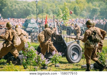 Gomel, Belarus - May 9, 2016: Back View Of Reenactors In Soldiers Uniform Of Soviet Armed Forces With Guns Recreating The Scene Of Battle Of WW2 Time On Celebrating Victory Day 9 May.