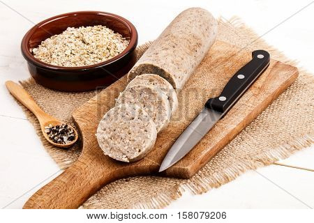 home made sliced irish white pudding with crushed pepper and oatmeal on wooden board