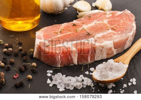 raw pork neck with thyme garlic olive oil peppercorn and coarse salt on slate