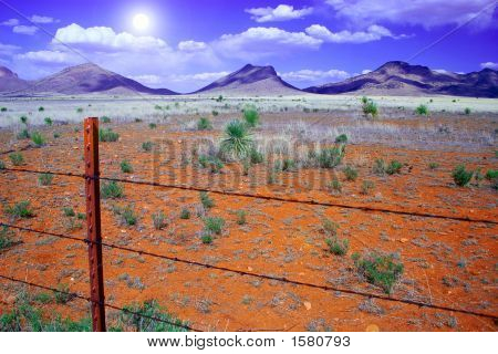 Barbed Wire Fence And Mountains