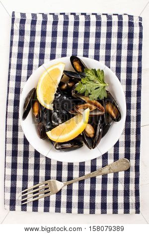 scottish mussels cooked in white wine sauce with lemon and parsley in a bowl on a kitchen towel