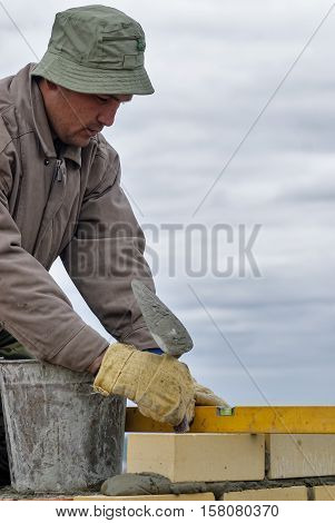 Tyumen, Russia - May 23, 2008: Construction of 18 floor brick residental house at streets intersection of Gercena and Chelyuskincev. Construction mason worker bricklayer installing brick with trowel