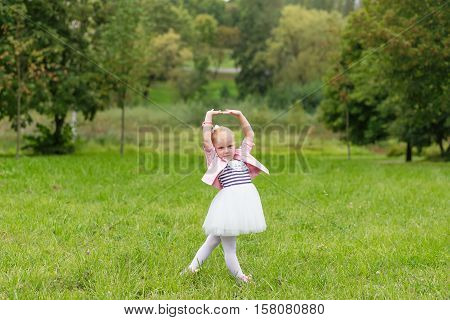 A Cute Little Girl In A Beautiful Dress And Sneakers Playing In The Park.