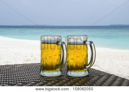 Beer mugs lying on a table in front of white sand beach and turquoise coloured ocean in Maldives.