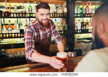 Cheeful attractive bearded young bartender giving glass of beer to customer in bar