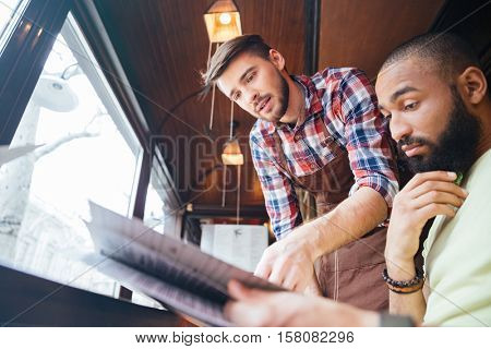 Handsome young server showing menu and helping to make an order to pensive bearded african man in cafe