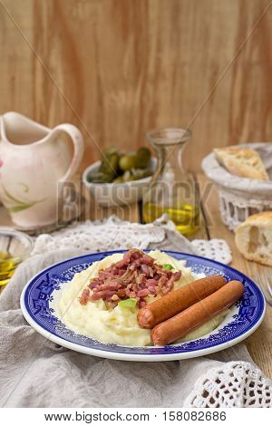 German style mashed potatoes with apples served with sausages and bacon
