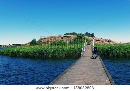 Wooden pier to the island. Bicycle on the wooden bridge. Karlskrona, Sweden