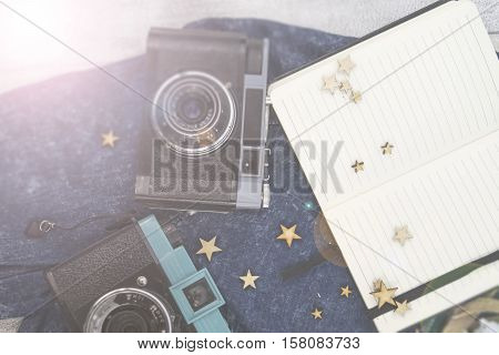Old photo camera and notebook on the wooden background. Accessories: branches, heather and jeans cloth