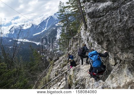 Tourists coming down from the steep slope in the mountains. Tatry, Poland