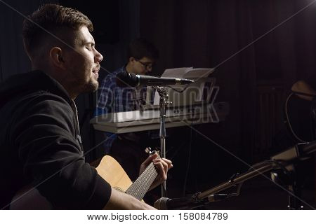 young guy playing guitar and singing into a microphone in a studio