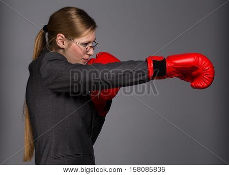 Strong and resolute young woman in dark grey business suit glasses and red boxing gloves stands in fighting pose with punch gesture on grey background