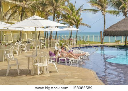 NATAL, BRAZIL, JANUARY - 2016 - Young adult couple resting at summer chairs at hotel swimming pool in Natal Brazil