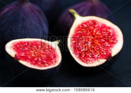 Fresh figs on black background. Beautiful blue violet figs with copy space