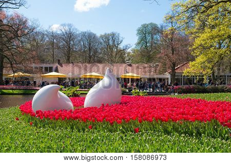 LISSE NETHERLANDS - APRIL 17 2016: Art objects in a field of blooming red tulips in the famous Keukenhof Gardens in the netherlands