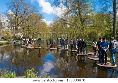 LISSE NETHERLANDS - APRIL 17 2016: Unknown tourists enjoying the water route in the famous keukenhof gardens in the netherlands