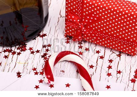 Red Candy Cane, Spotted Present Box And Bottle Of Champagne On White Wooden Table