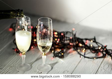 Cold Champagne Flutes Stand On Wooden Floor Behind Christmas Garland