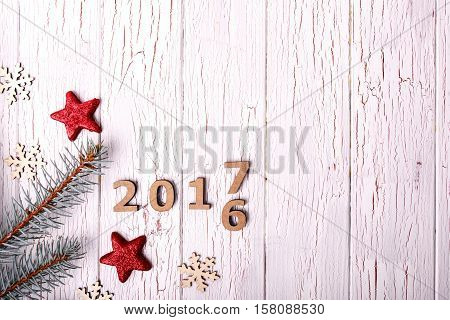 Red Stars And Fir Branches Surround Wooden Numbers 2016 And 2017