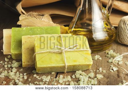 Collection of handmade, natural organic soap and cosmetic oil on wooden background. Spa products. Vintage toned