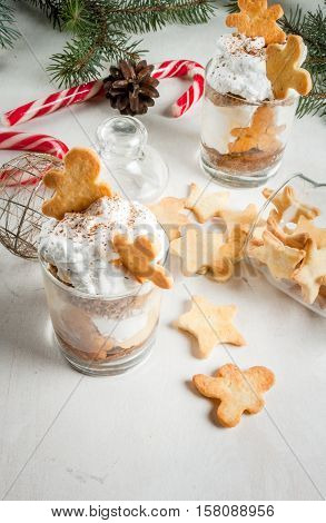 Christmas dessert funny food for children or party. Ginger Trifle with gingerbread in form of men diving in the drifts of whipped cream. Copy space