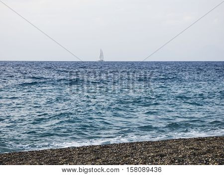 Sailboat on sea with beach at Sicily