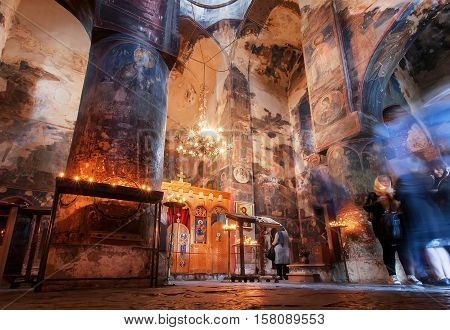 GREMI, GEORGIA - OCT 1, 2016: People praying with candles in dark interior of Church of the Archangels with frescoes on 1 October, 2016. The Curch was built in 16th century in Kakheti Georgia.