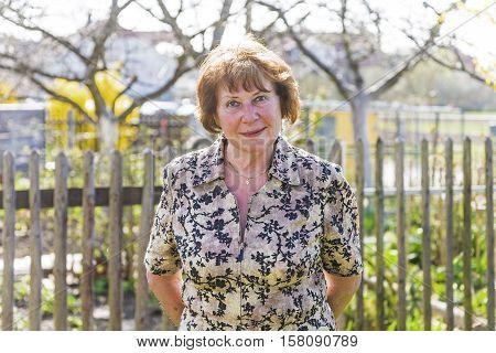 happy elderly woman is standing proud in her garden and smiles