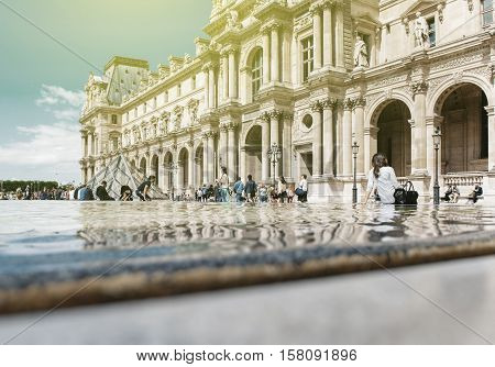 PARIS FRANCE - AUG 18 2014: Group of tourists visitig Louvre - Cour Napoleon in summer with relaxed people sitting on the edge of fountain near the Pyramid by the architect Ieoh Ming Pei. Louvre is the most visited museum in the world. Paris sightseeing