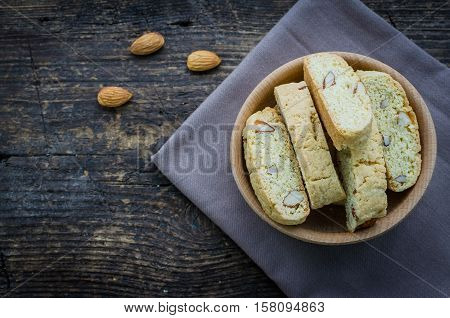 Italian cantuccini cookies in a bowl with almonds. Traditional italian almond cookies biscotti on wooden background. Homemade Almond cookies with space for text on wooden table. Top view. Copy space.