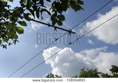 Electric wire of trolley bus and blue sky with fluffy clouds