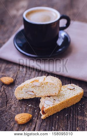 Good morning concept - breakfast frothy espresso coffee accompanied by delicious Italian almond cantuccini biscuits. Traditional italian biscotti cantuccini on wooden table. Selective focus. Toned image.