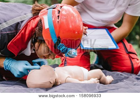 Cpr practice of woman and man on cpr baby dummy outdoors