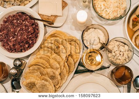 High angle closeup of a dining table full of a variety of delicious traditional food and wine
