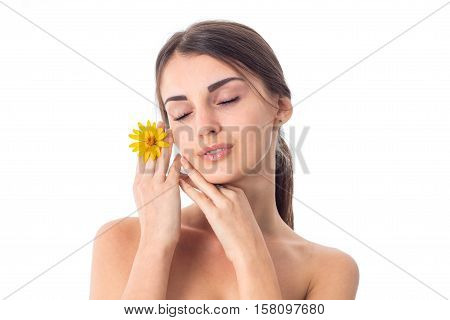 Young attractive girl takes care her skin with closed eyes and yellow flower in hands isolated on white background. Health care concept. Body care concept. Young woman with healthy skin.
