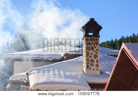 Brick chimney smoke of ethno house roof winter snow in mountain forest