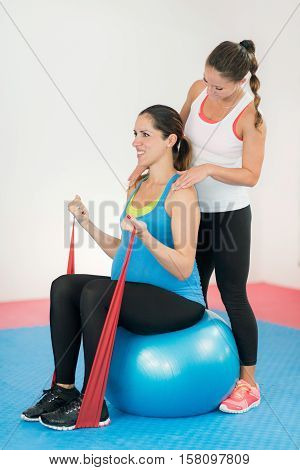 Third trimester pregnant woman exercising. Soft easy training with fitness ball and resistance band. Fitness instructor giving support.