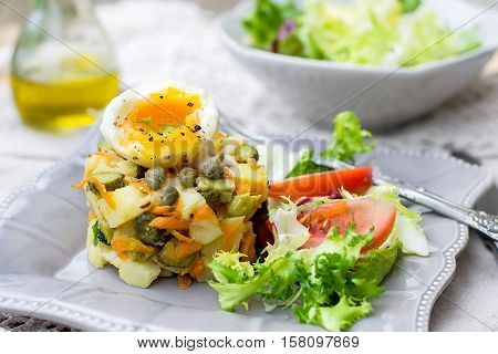 Potato salad with pickles carrots capers and soft-boiled egg