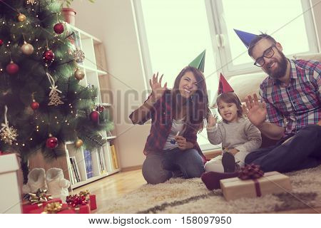 Beautiful young family having fun together for Christmas holidays sitting on a living room floor next to a nicely decorated Christmas tree smiling and waving