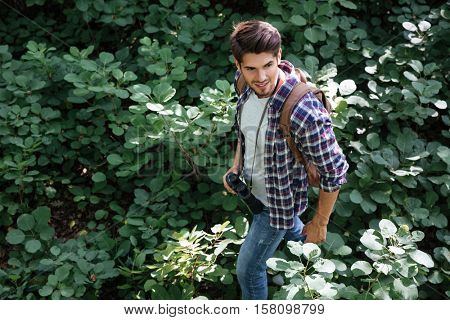 From above image of man with binoculars in forest. stands sideways. looking away.