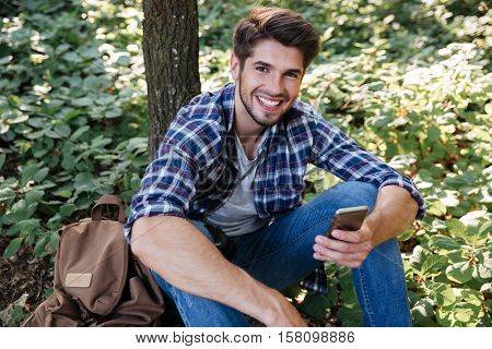 Happy man sitting in forest. top view. man with phone and backpack. near the tree. looking at camera