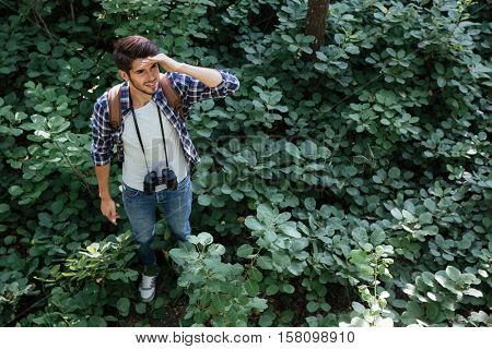 Man lost in forest. man in shirt with binoculars and backpack