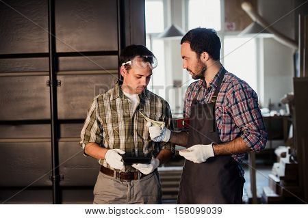 Two carpenters are talking and holding papers and ruler. One of them is wearing safety mask. Carpentry shop background.