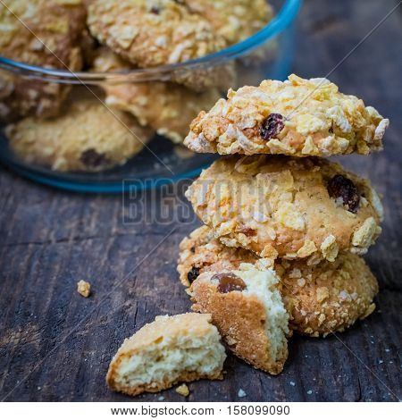 Homemade cornflakes and raisins cookies on old wooden table. Freshly baked corn flake cereal cookies on rustic background. Selective Focus.